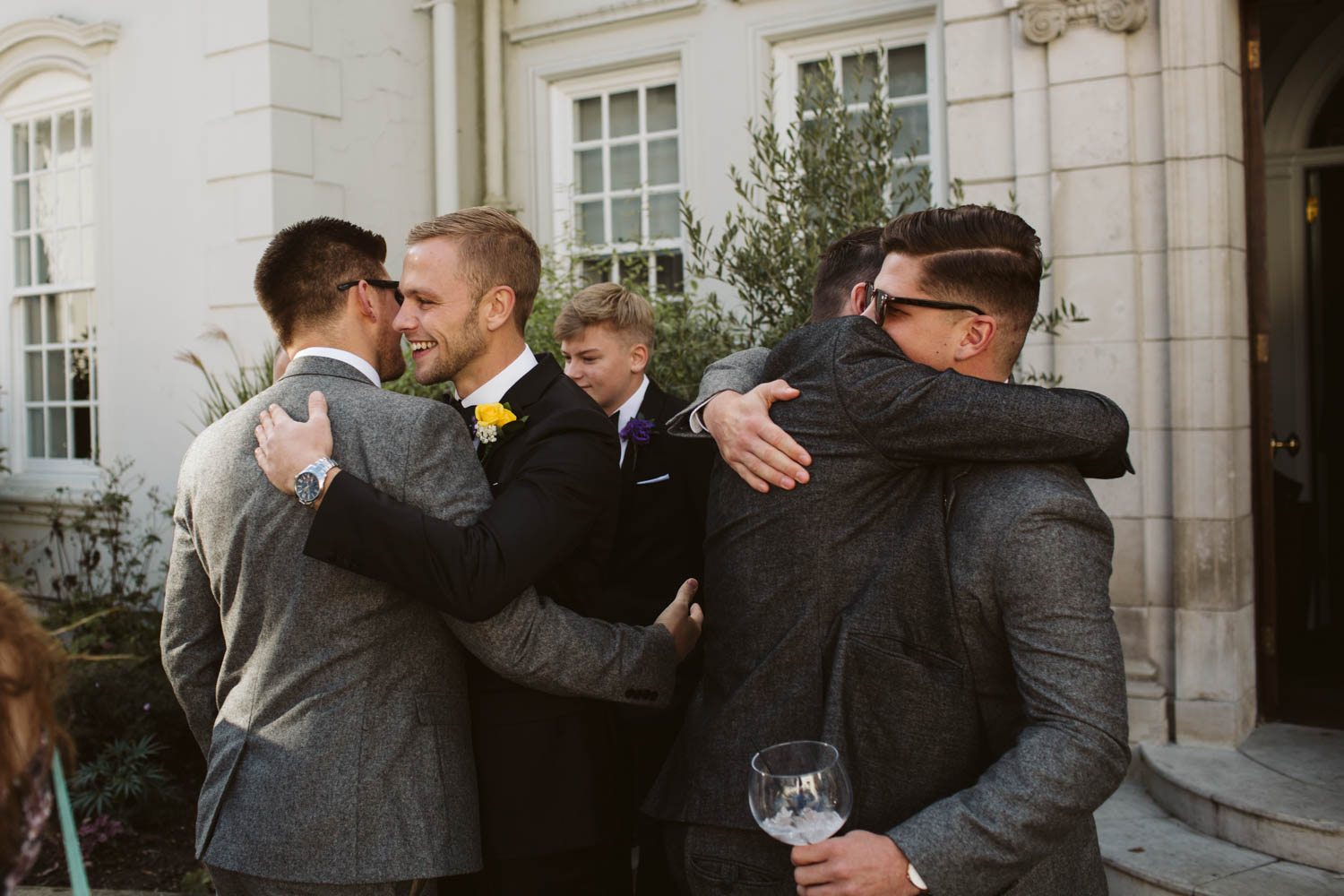 the groom and Brest man hugging with guests