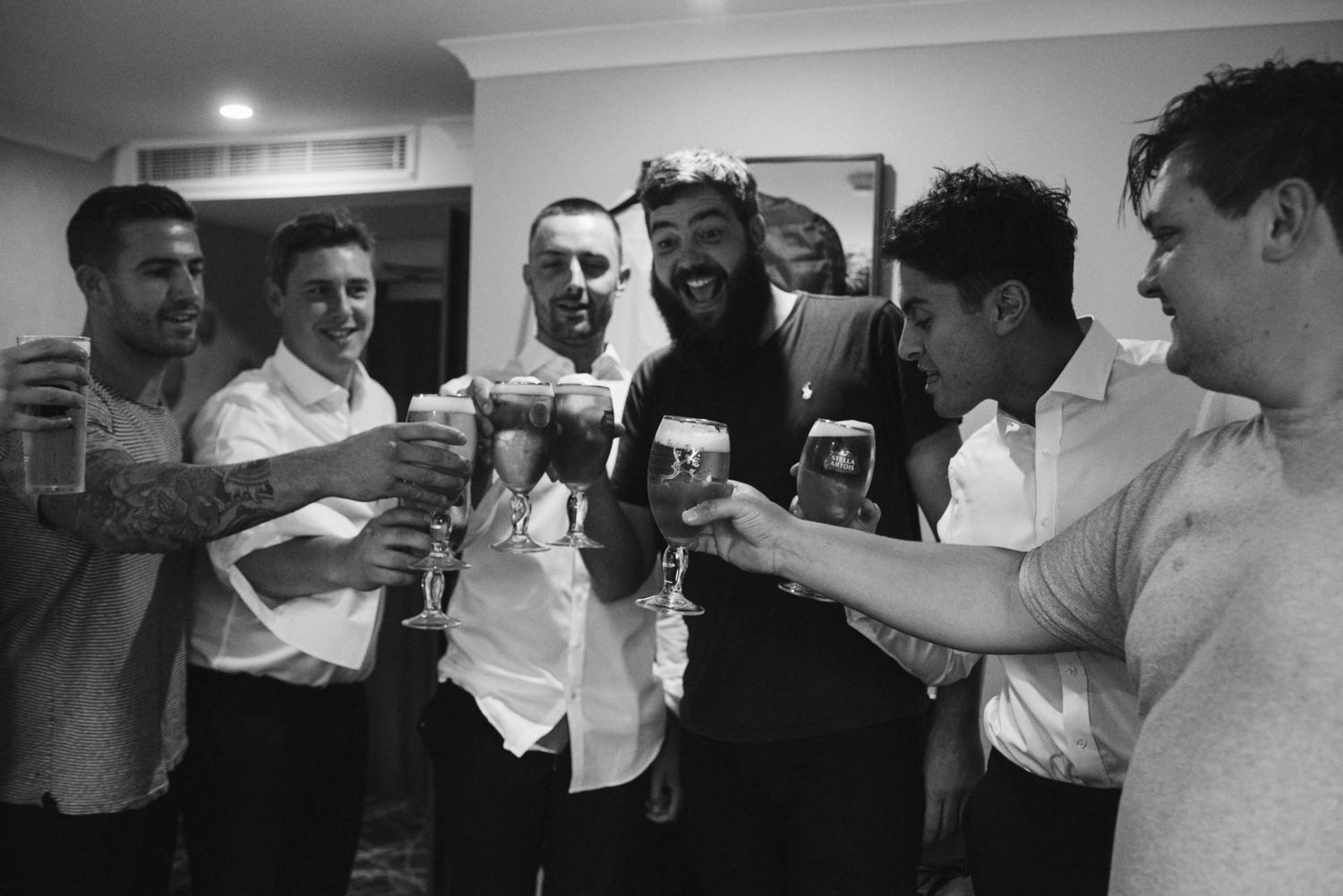 groomsmen clinking beer glasses