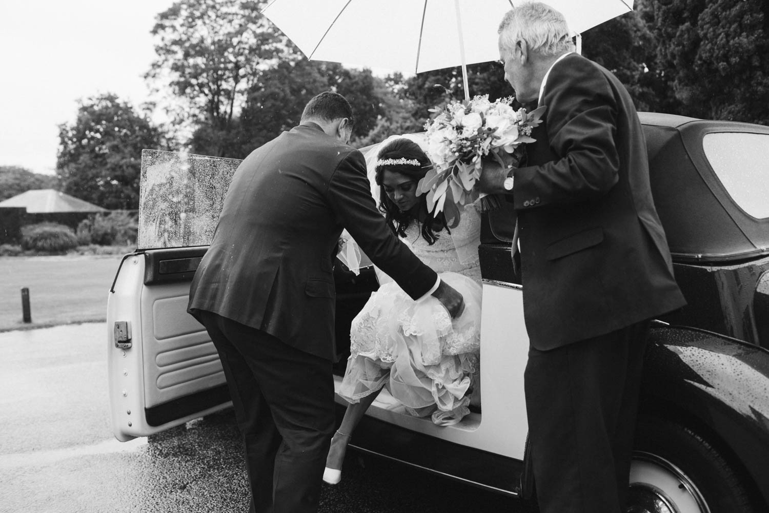 the bride leaving the car in the rain