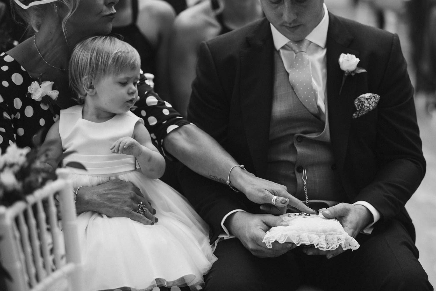 cute flower girl looking at the rings