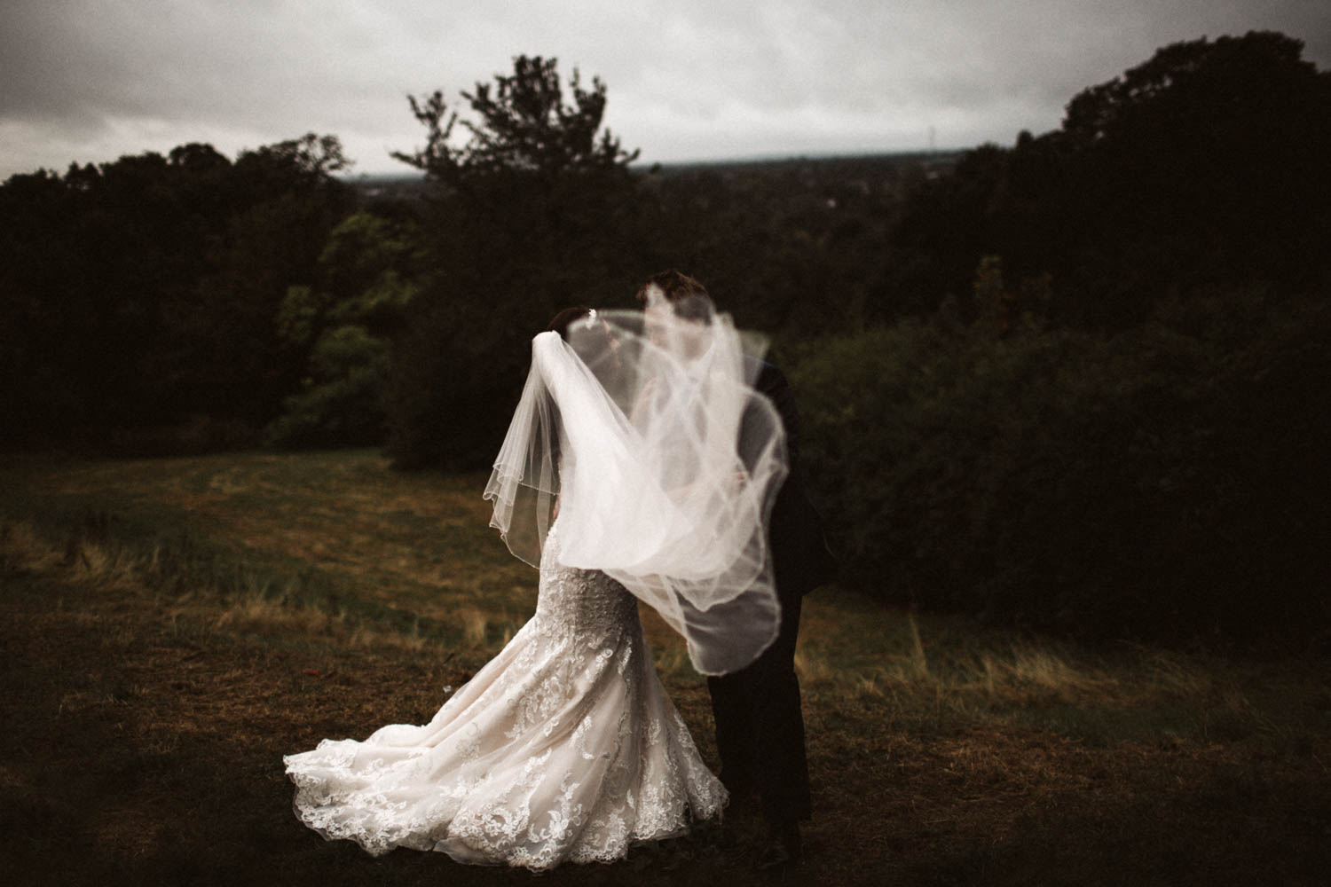 a creative portrait of the couple in the wind and rain