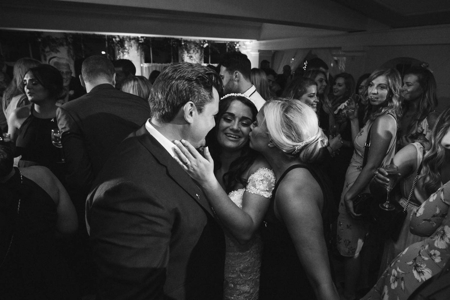 brides getting kissed from all angles by friends