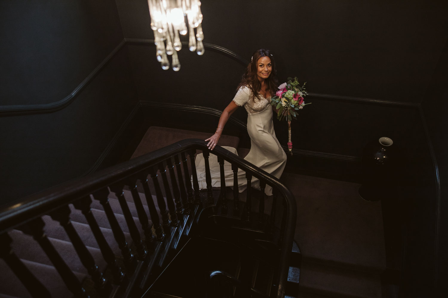 Bride on staircase holding bouquet