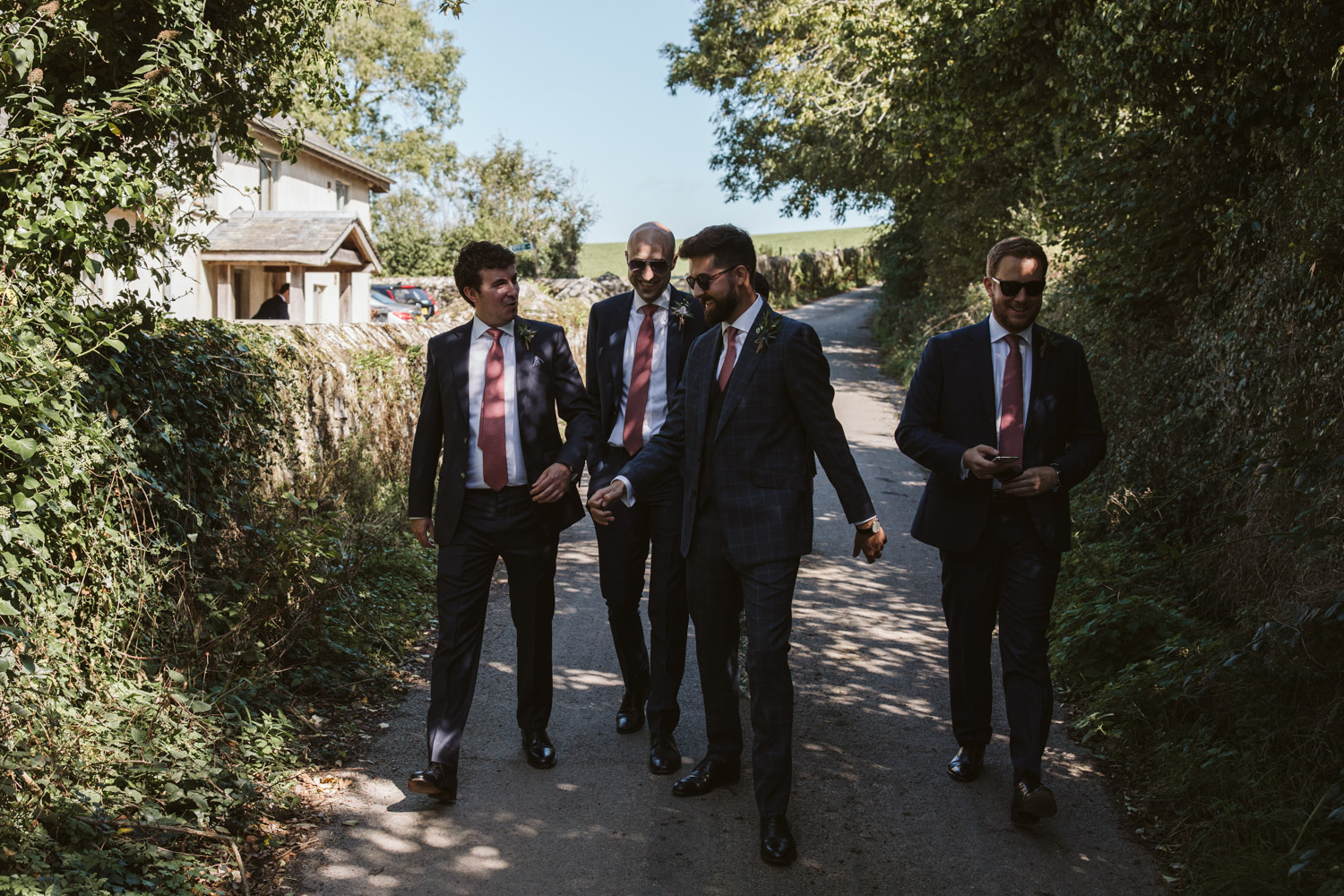 groomsmen walking through Carswell farm to the clifftop