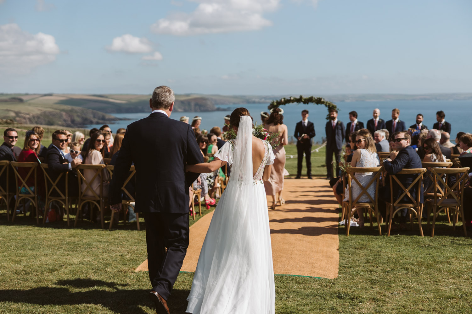the bride and father walking down the clifftop aisle