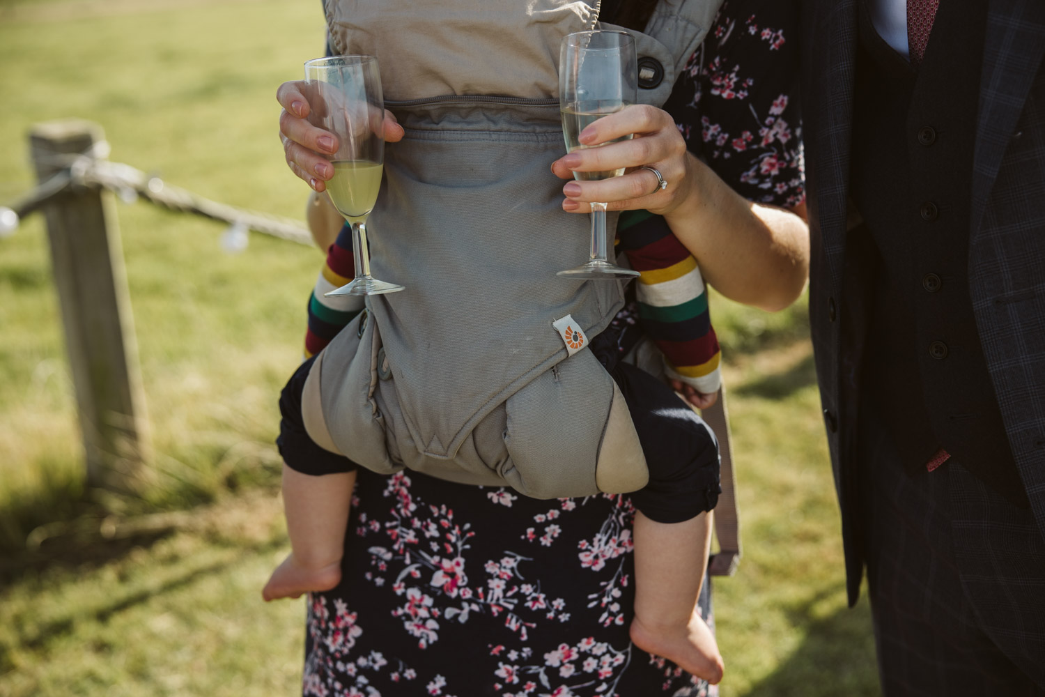 a baby in a sling with the legs mirroring the mum carrying two champagne glasses