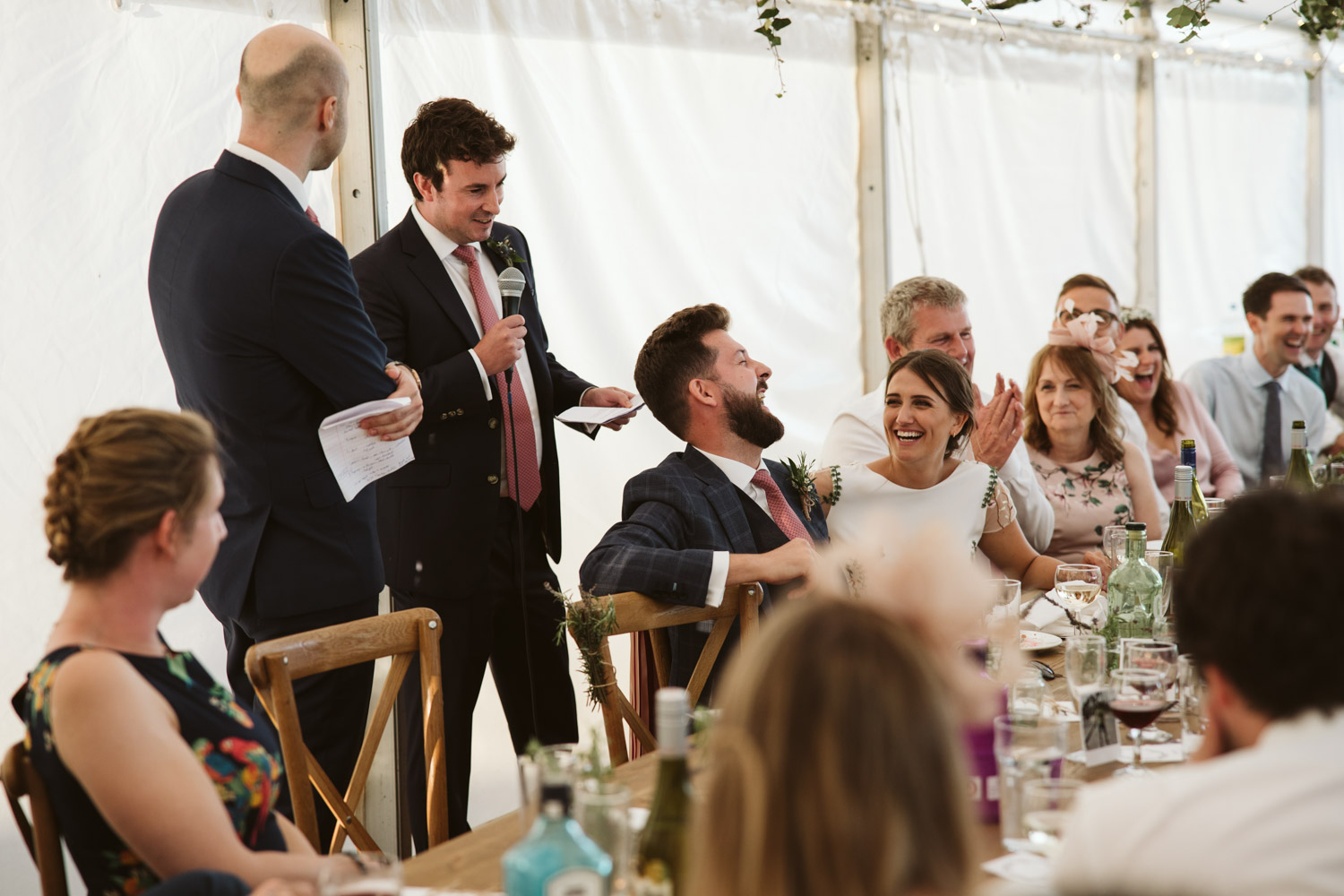 the best man embarrassing the groom and laughing