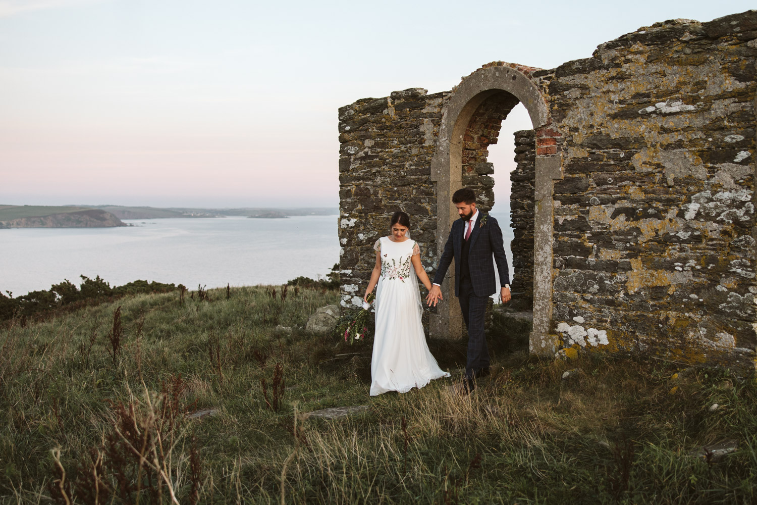 the couple walking away from the ruins with a beautiful scenery view