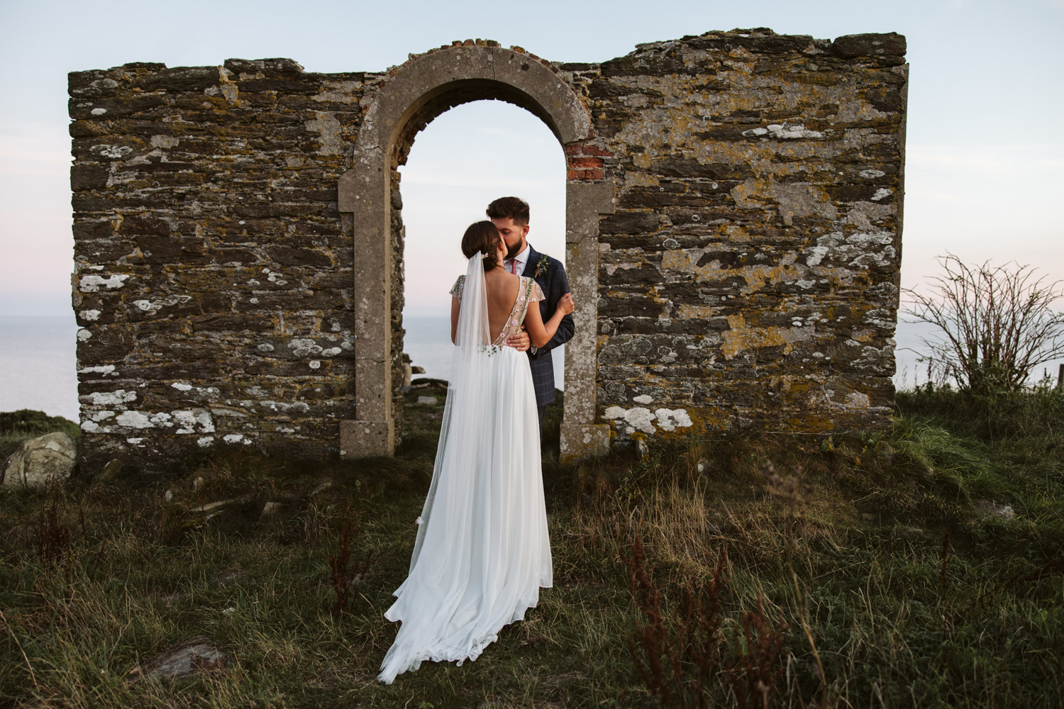 cool composition of the couple kissing next to ruins