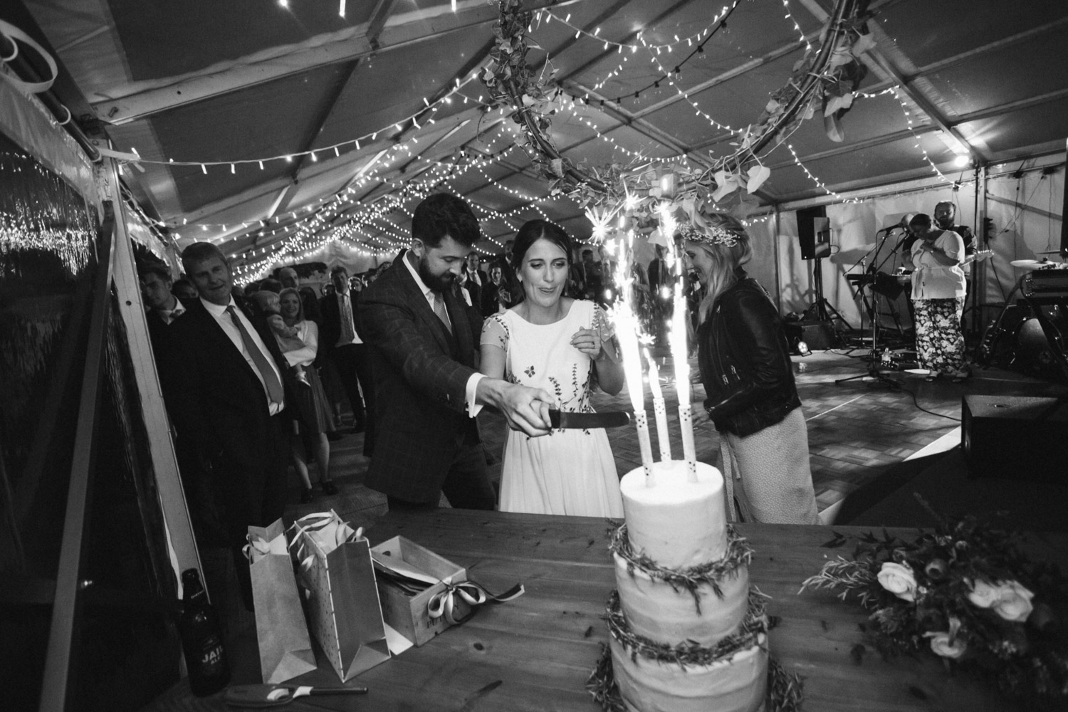 the newlyweds lighting fireworks on the wedding cake