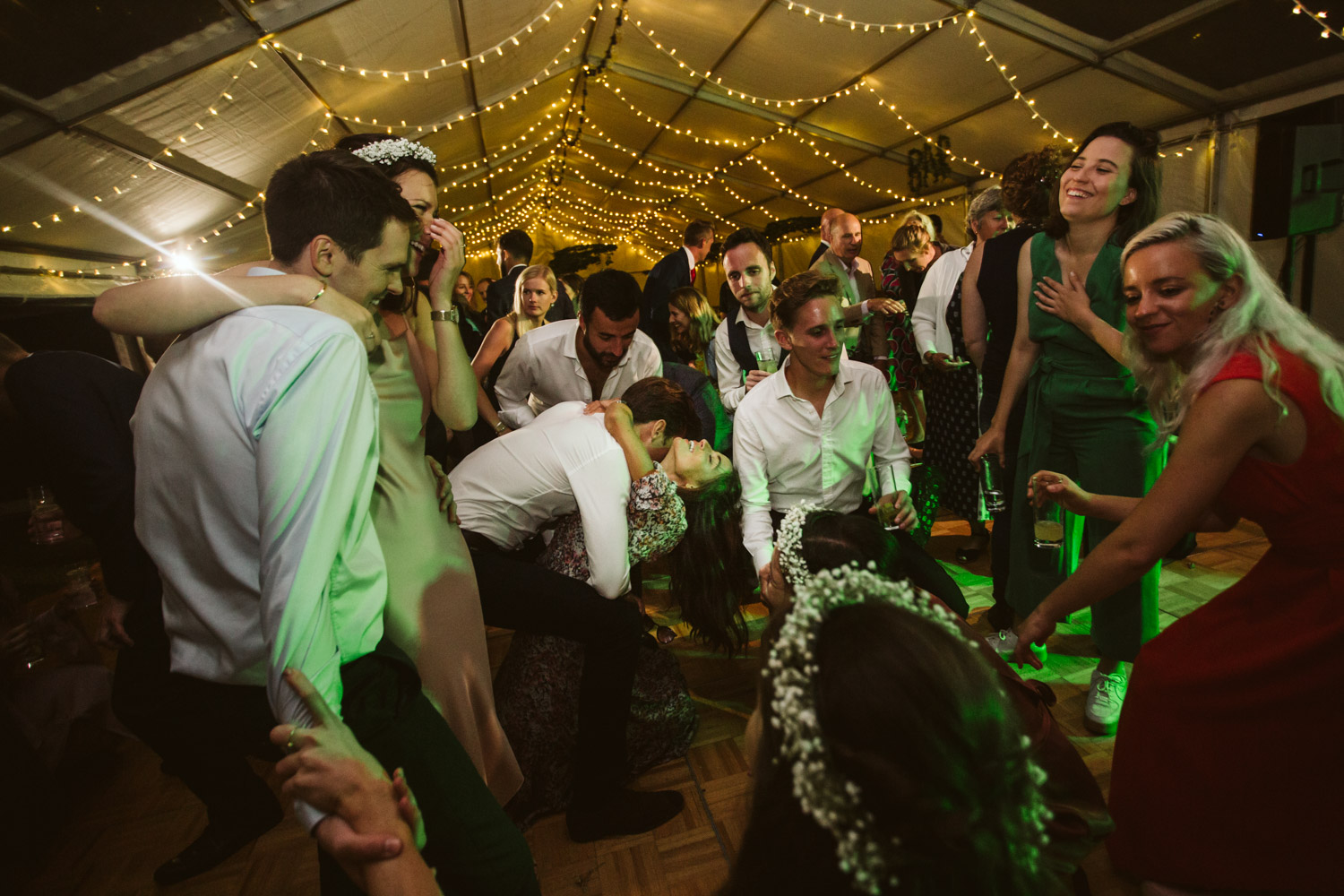 a couple sharing some love on the dance floor, surrounded by guests