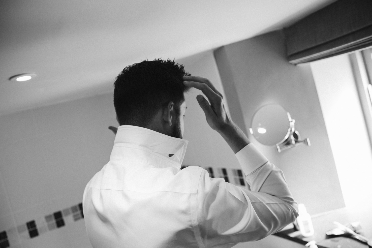 groom finishing his hair in the mirror