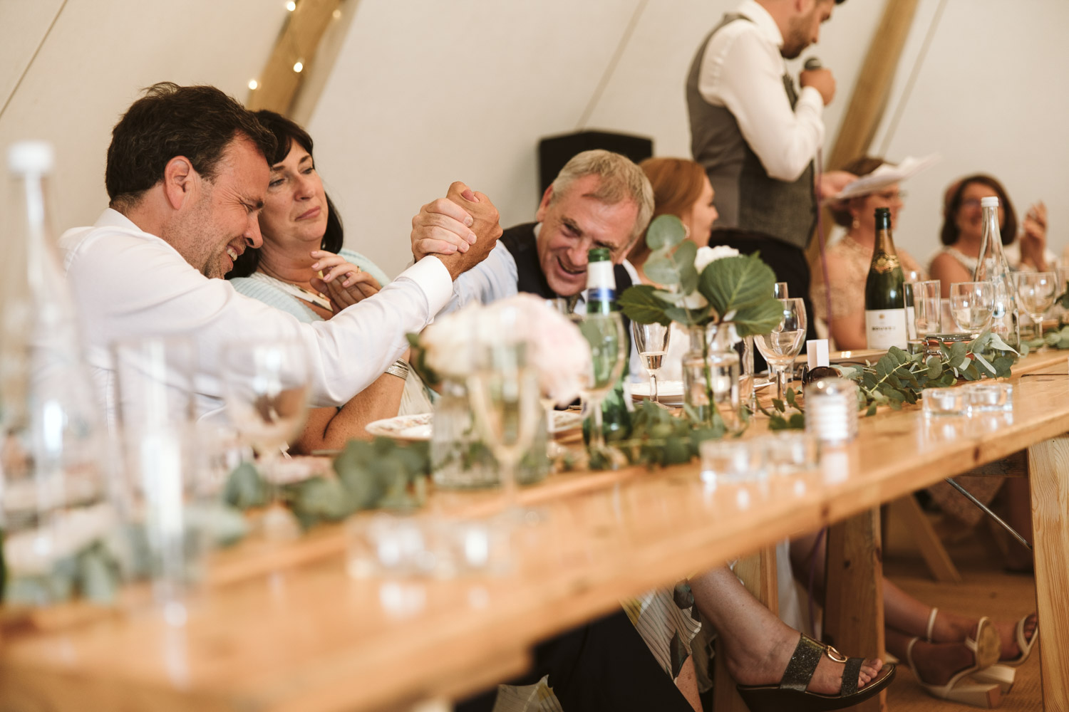 the father of the bride and groom share a fist pump