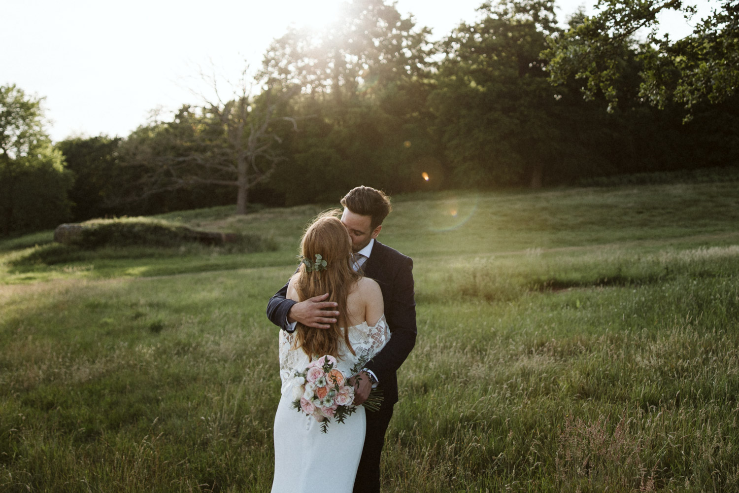 the bride and groom share and embrace in the setting sun