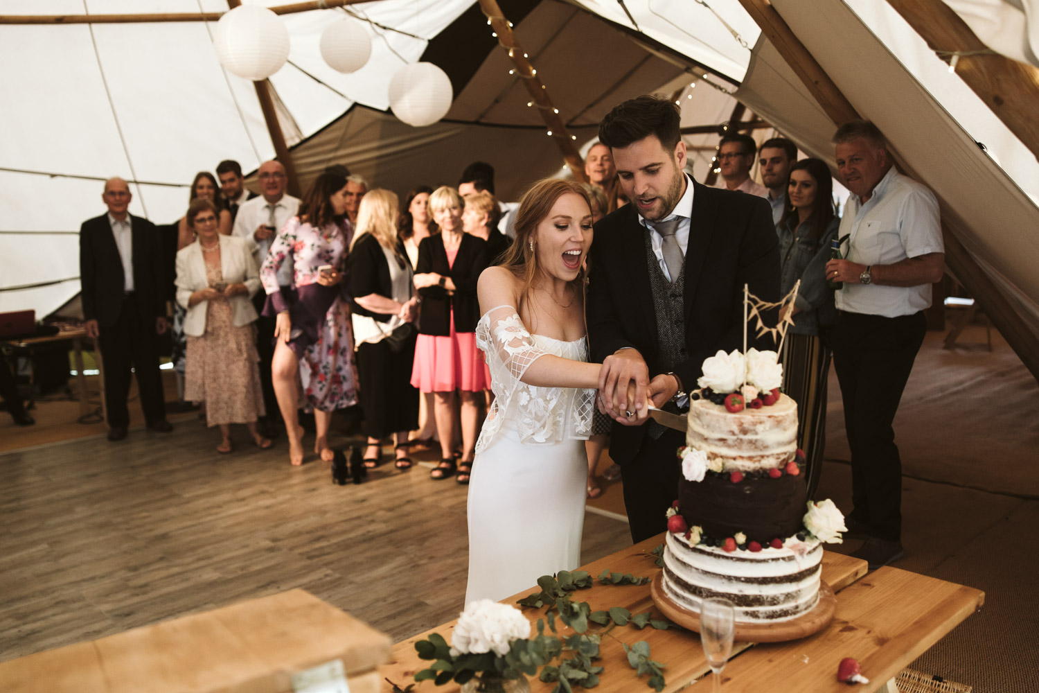 the couple are cutting the wedding cake surrounded by cheering guests