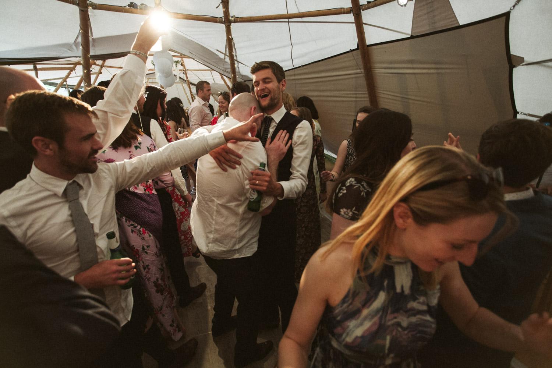 groomsmen hugging on the dance floor