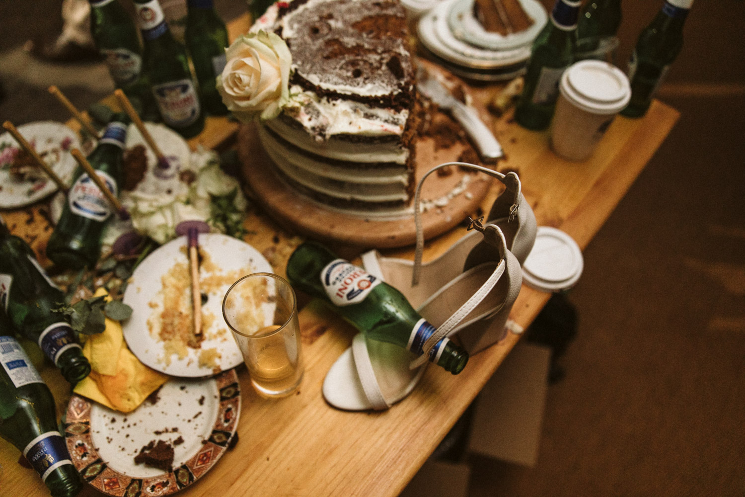 the half eaten cake and table is a mess of empty bottles and the brides shoes are there