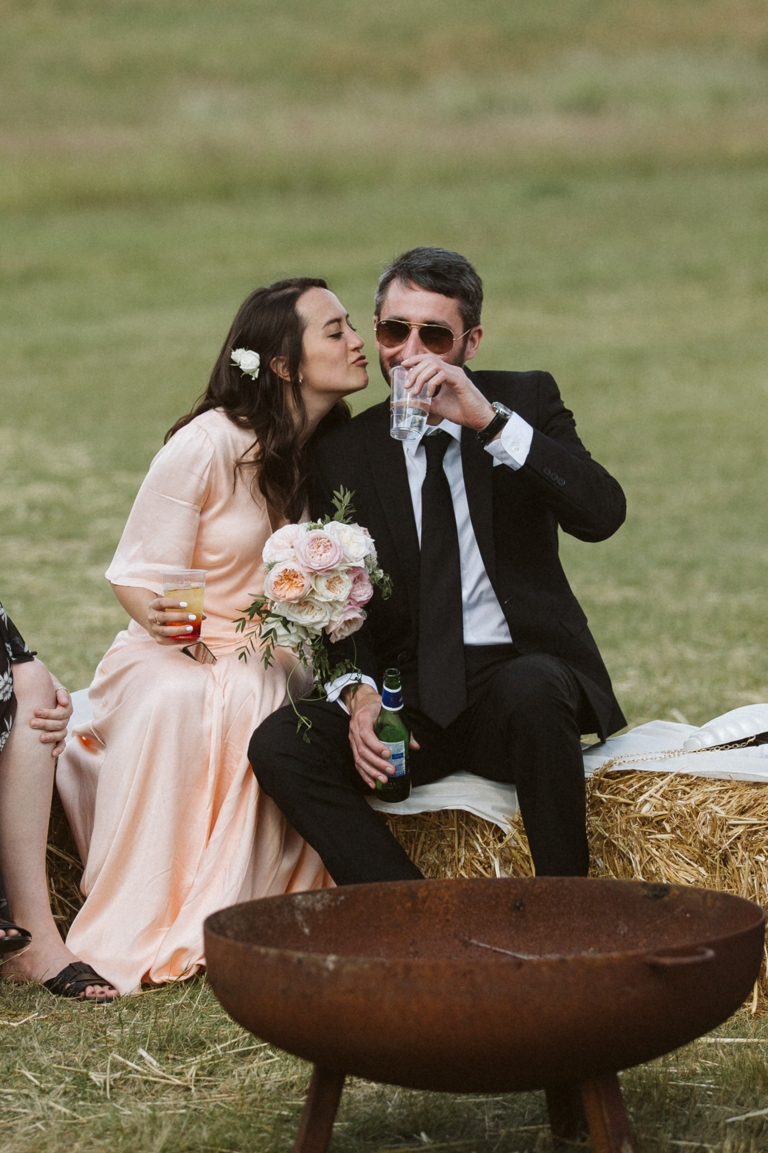 an intimate moment on hay bales with a bridesmaid and her partner