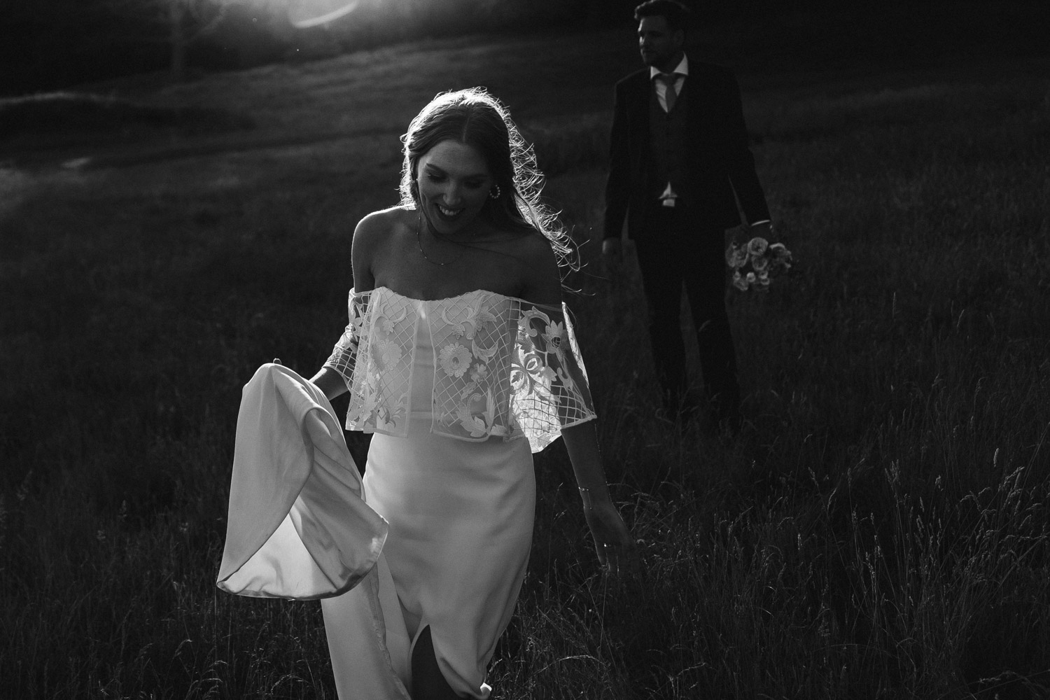 a glamorous and dramatic photo of the bride and groom in the secluded field