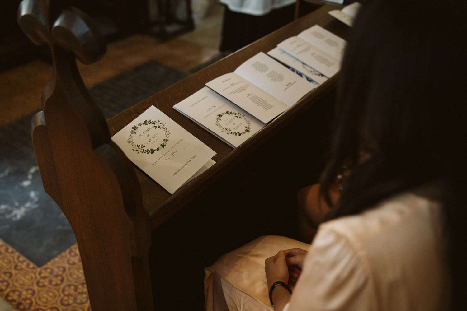 the beautifully designed order of service held by a bridesmaid