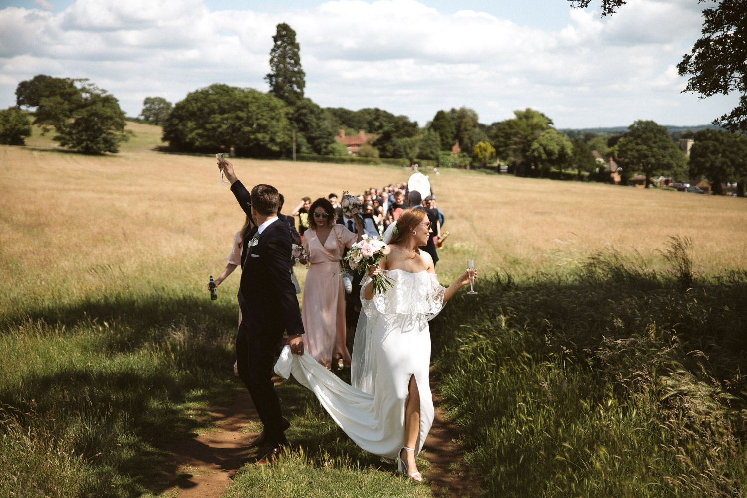 the bride and groom leading the guests down the hills in the hidden valley to their tipi