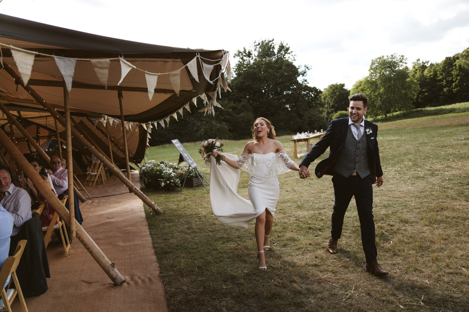 the bride and groom look really happy as they are welcomed into the tipi
