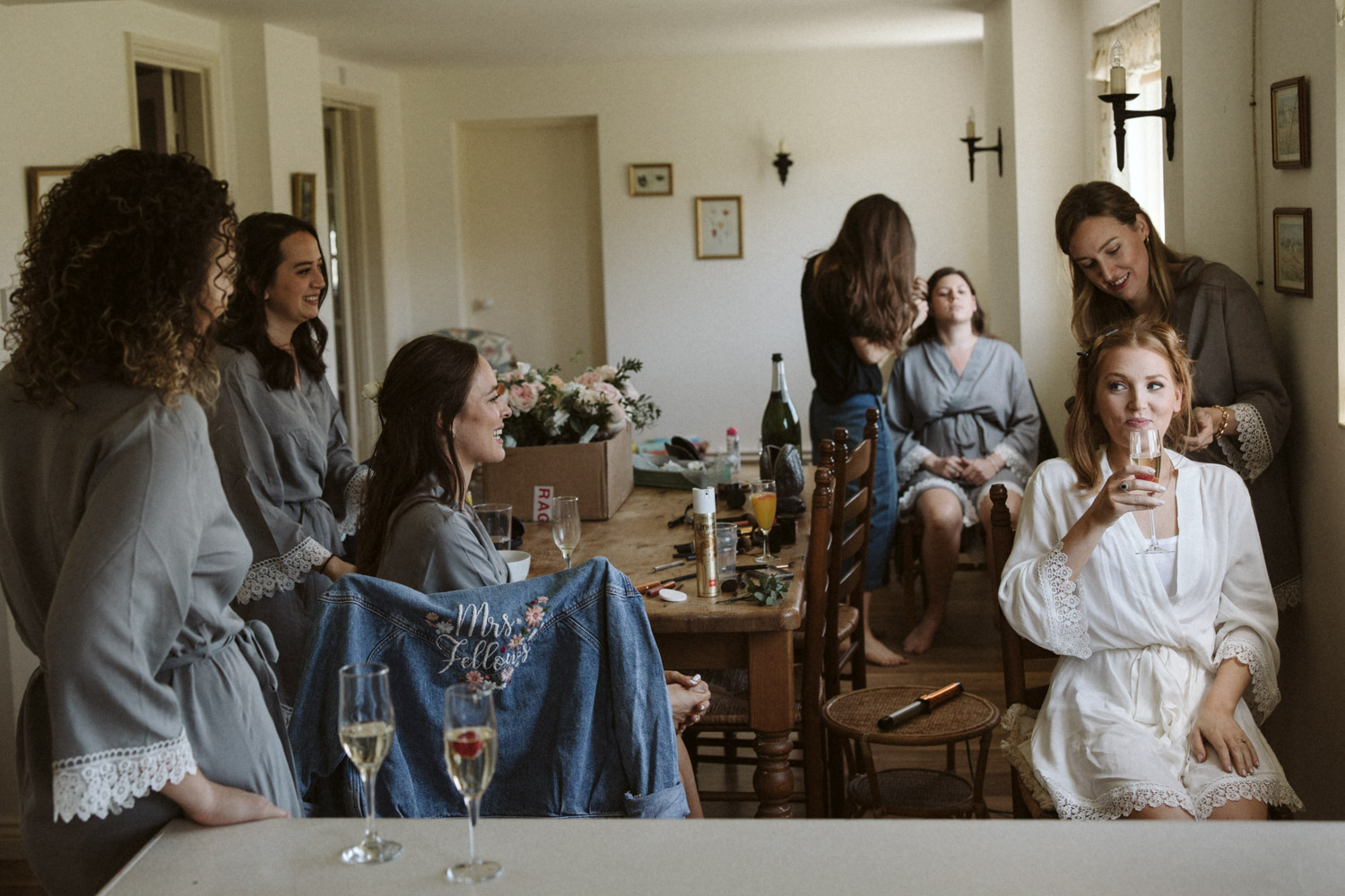 The bride and bridesmaids drinking and laughing while having their hair styled