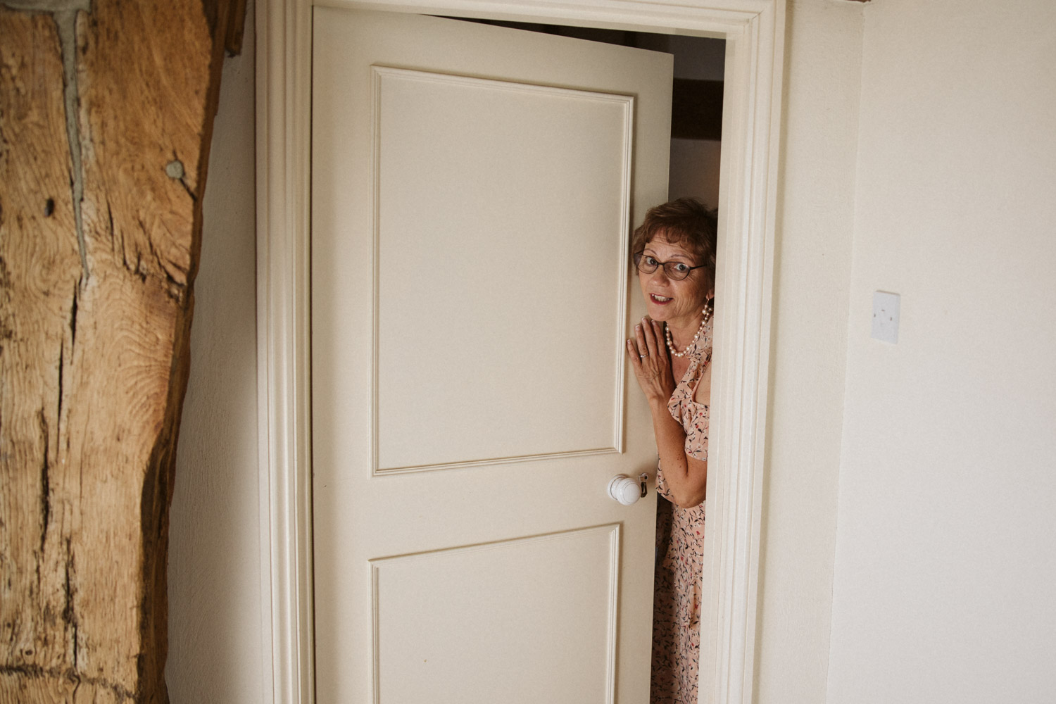the mother of the bride opening the door to her preparation room