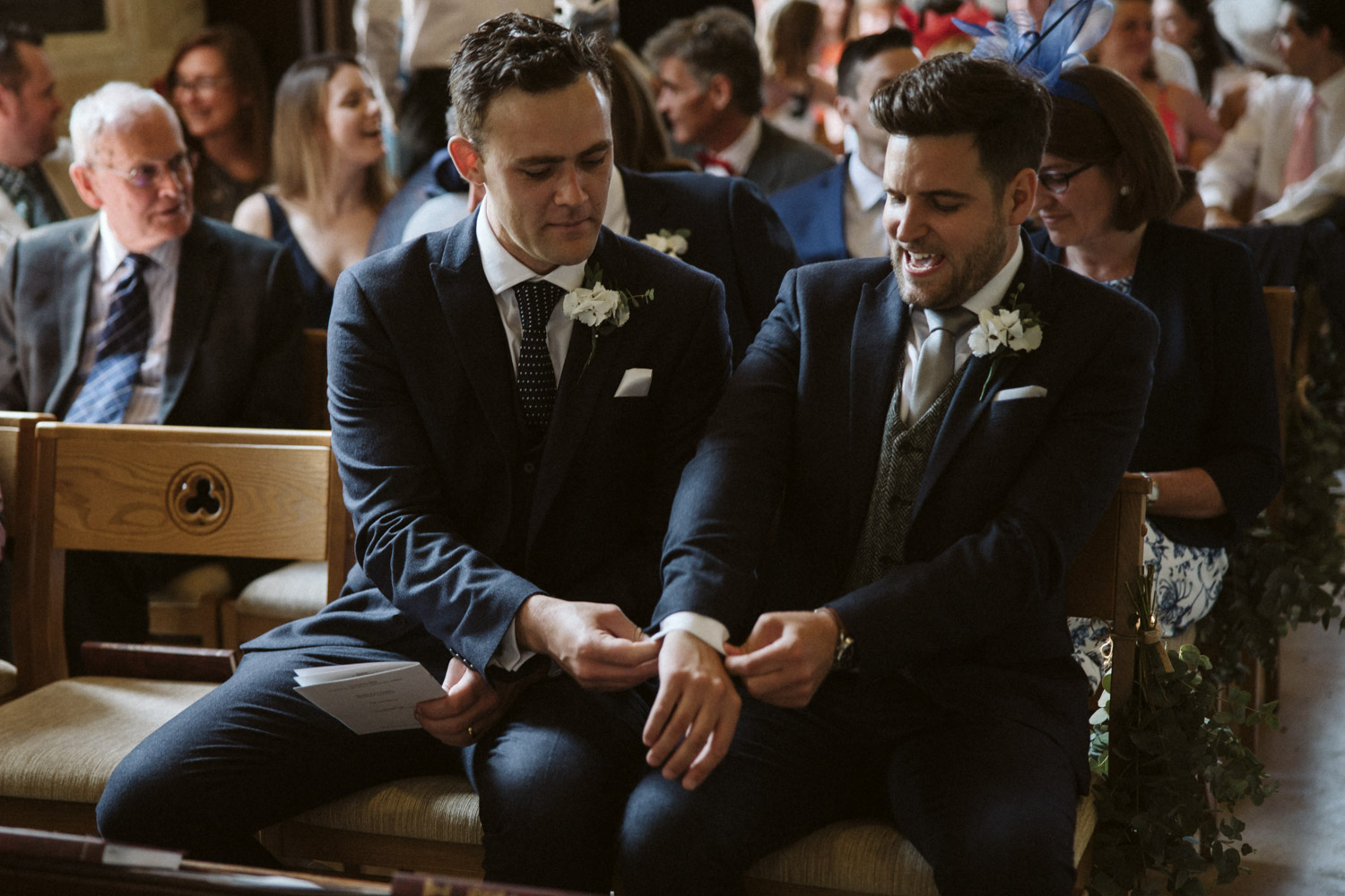 the best man and groom sitting at the altar