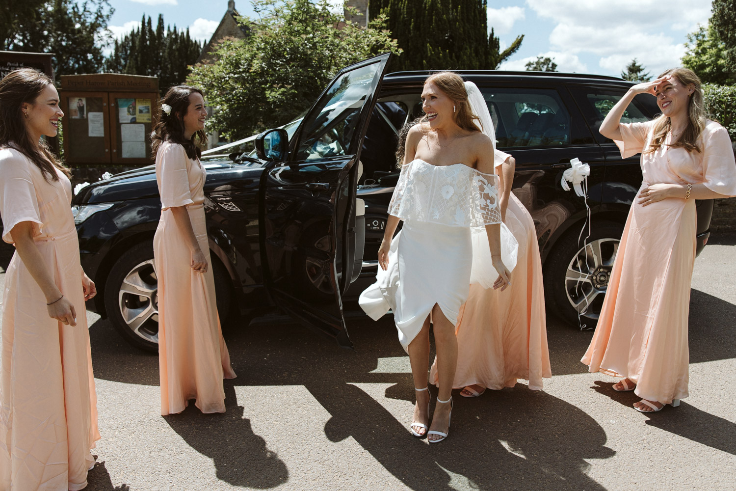 the bride and bridesmaids arriving at the church in beautiful sunlight, the bride is beaming with happiness
