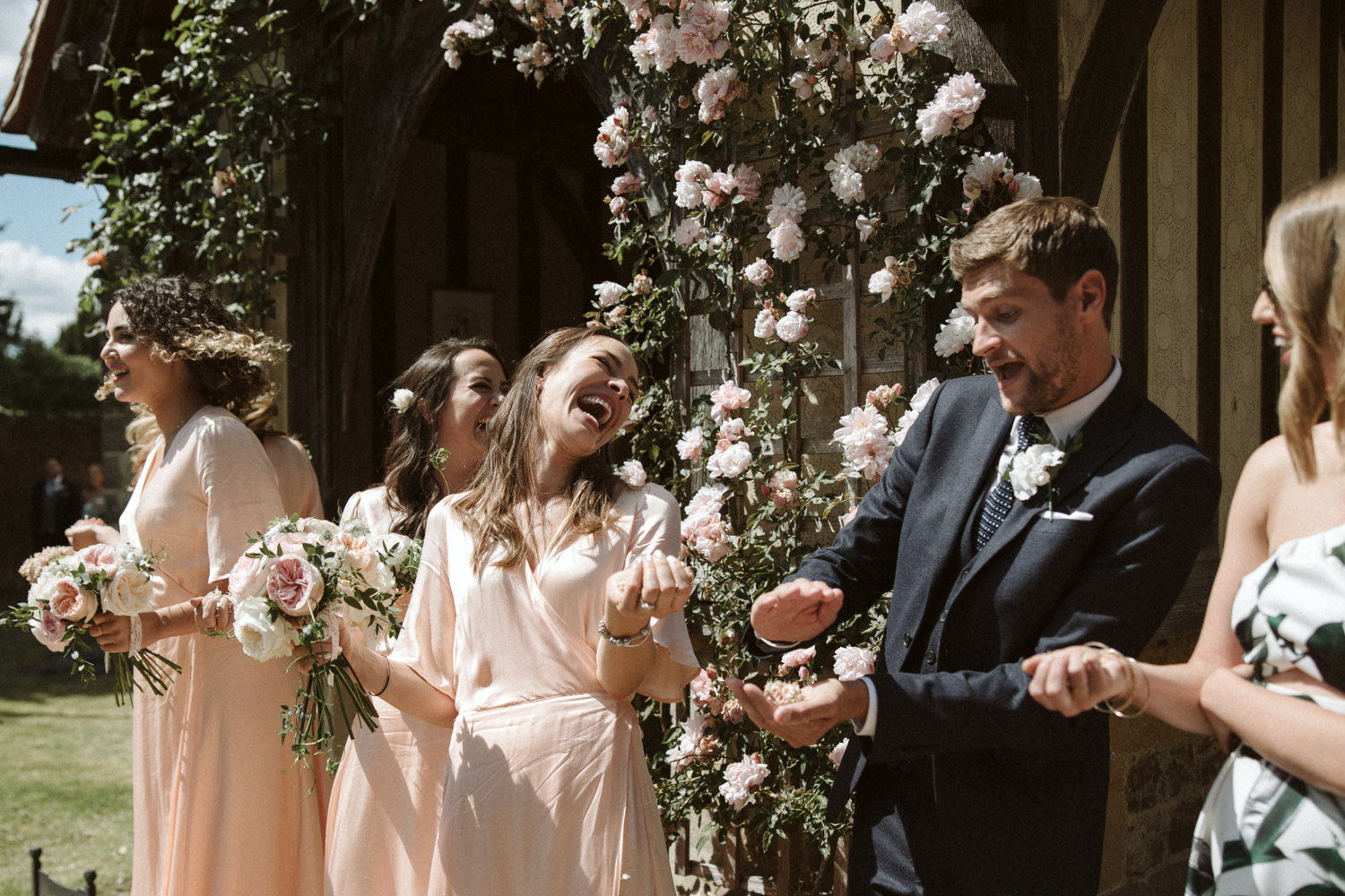 beautiful guests laughing about to throw confetti in front of a beautiful floral arch