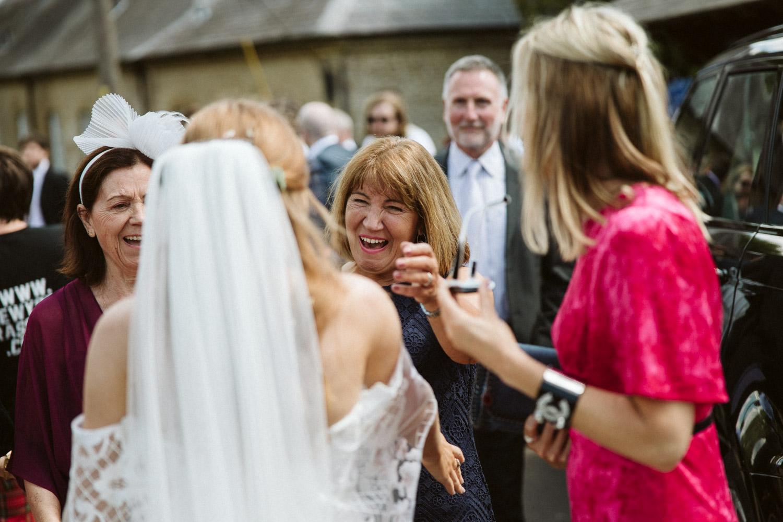happy guests cuddling the bride