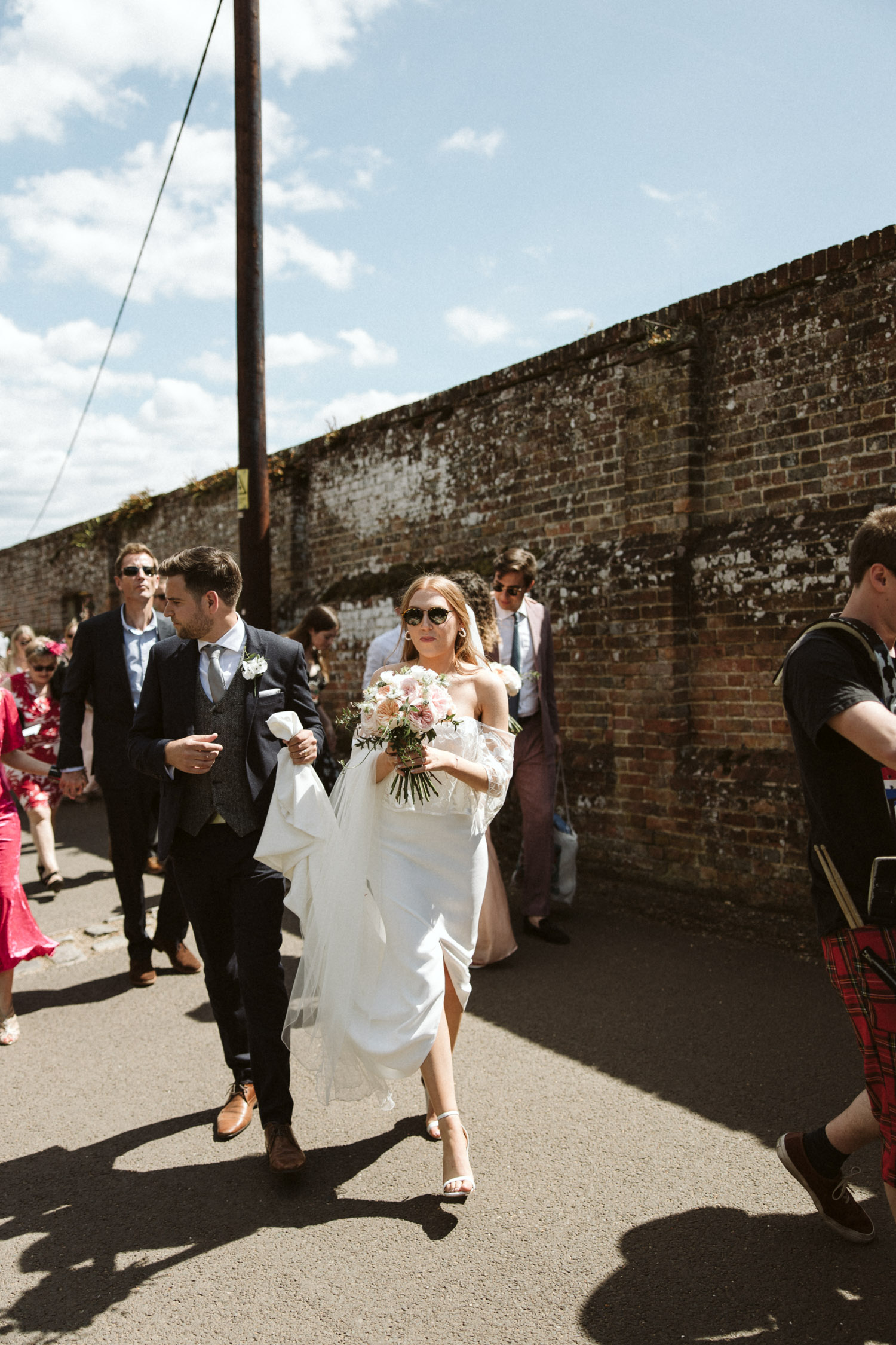 the glamorous bride leading guests through the village