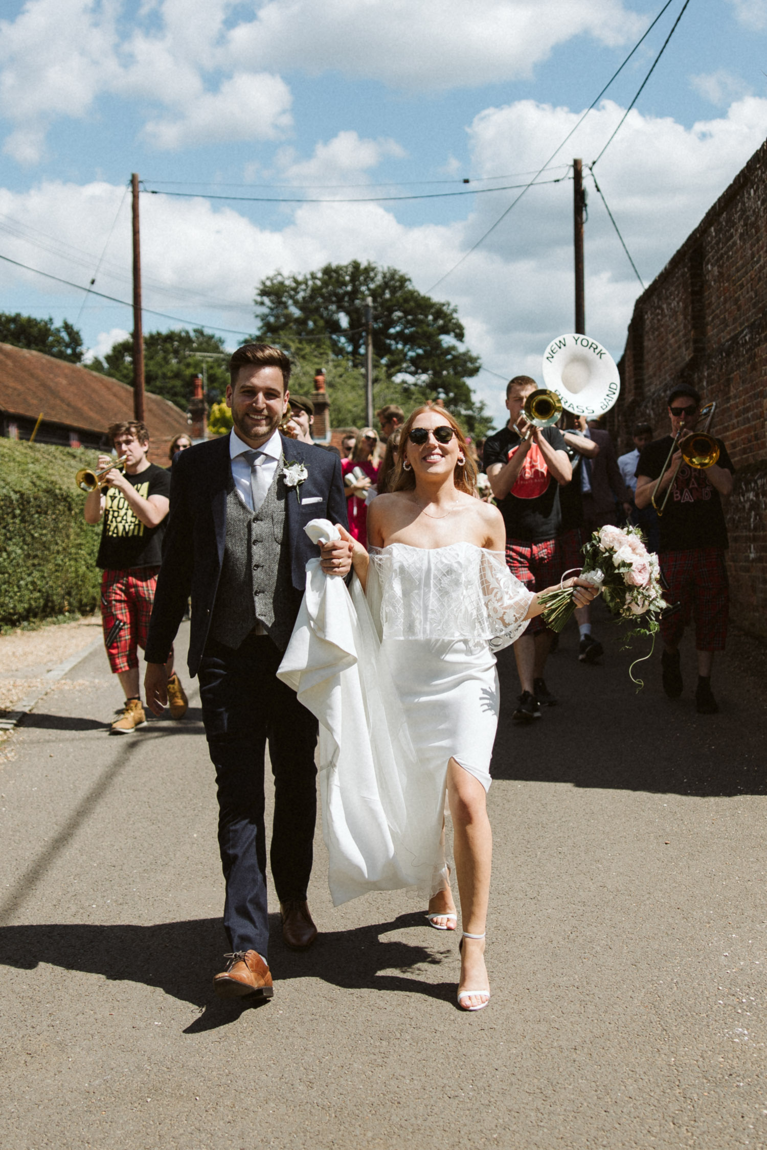 the bride and groom and the New York brass band leading guests through the village